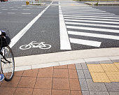 Cycle path alongside pedestrian crossing traversing multi-lane road in Kyoto, Japan.