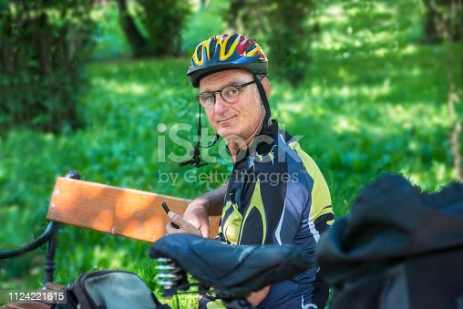 518659854istockphoto Cycling. A senior cyclist sits on the bench and uses a mobile phone 1124221615