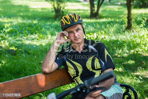 istock Cycling. A senior cyclist sits on the bench and uses a mobile phone 1124221824