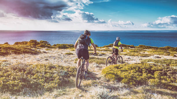 cycling along coastline - mountain biking stock photos and pictures