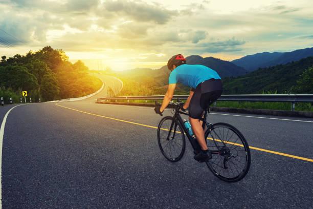 Radsport-Wettbewerb, Radsportler mit hohem Tempo auf der Bergstraße, Sportsmen-Bikes am Morgen, Vintage-Farbe, selektiver Fokus, Sportkonzept, Niederwinkel-Ansicht, Business-Wettbewerb – Foto
