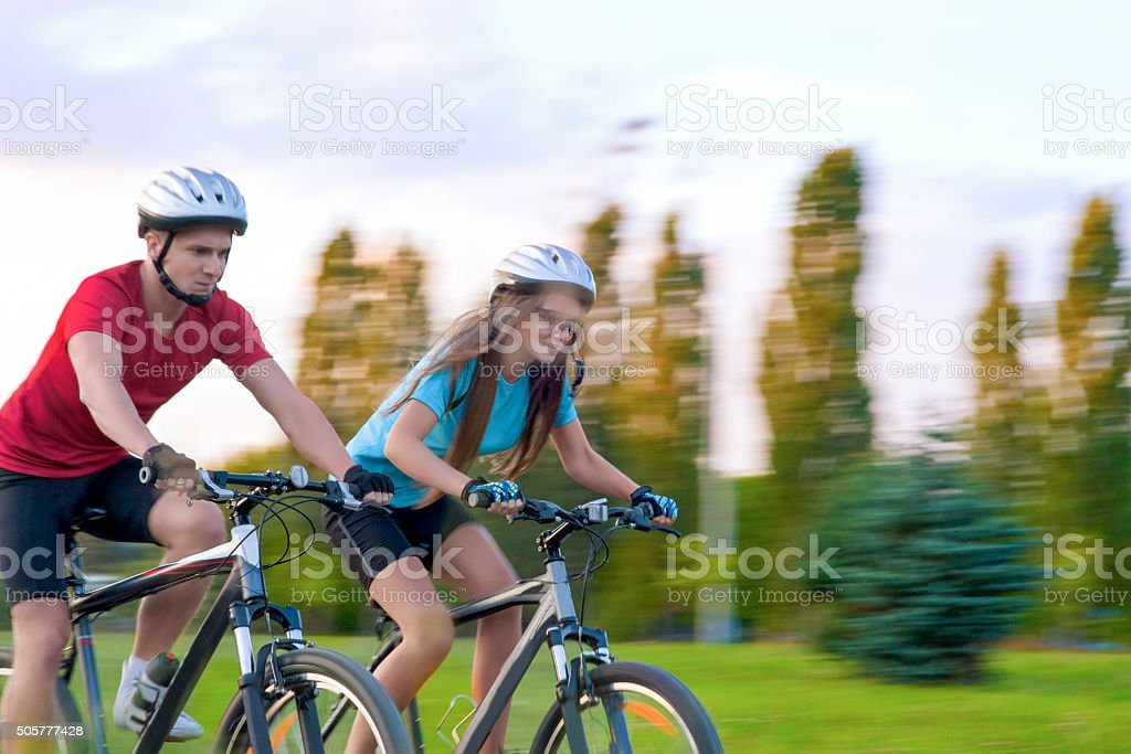 Cycling Concept: Young Caucasian Couple Having a Speedy Bicycle stock photo