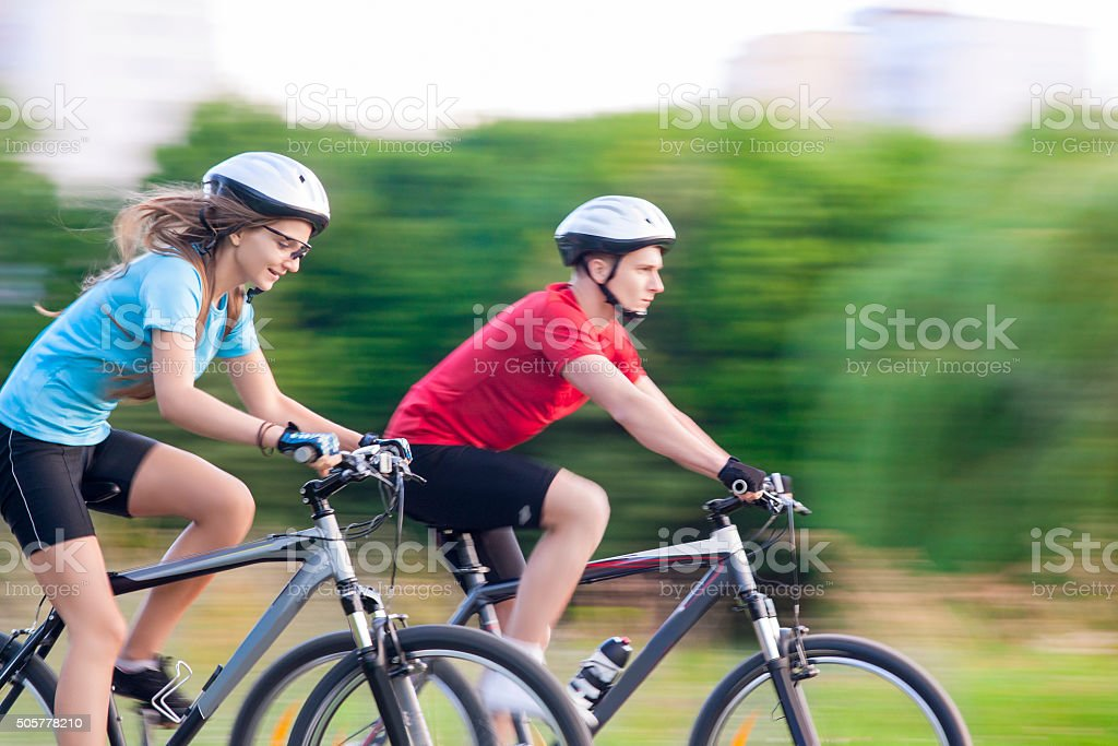 Cycling Concept: Young Caucasian Couple Having a Sppedy Bicycle stock photo