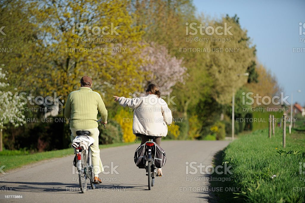 Cycling couple on a country road in the Netherlands royalty-free stock photo