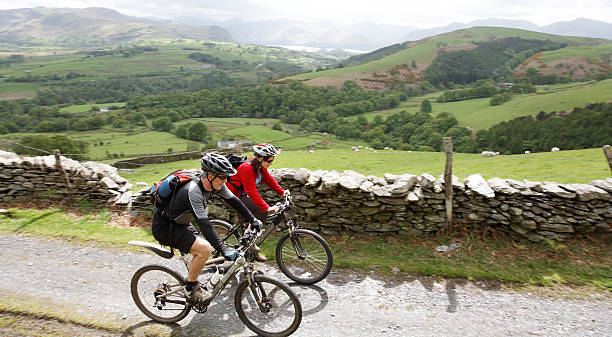 Cycling couple  english lake district stock pictures, royalty-free photos & images