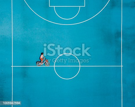 Cycling in a surreal world. Aerial view. Conceptual realism trend. Young adult woman cycling in a basketball court.