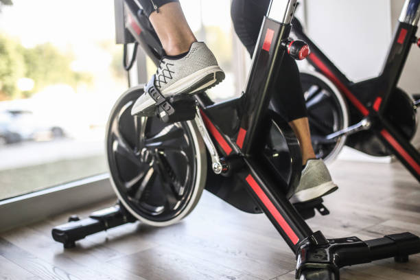 Cycling in gym Unrecognizable Caucasian man riding a stationary exercise bike in gym. exercise bike stock pictures, royalty-free photos & images