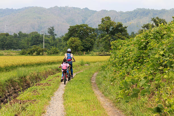 cycling in the country Two people make cycling in a Japanese rural scenery. satoyama scenery stock pictures, royalty-free photos & images