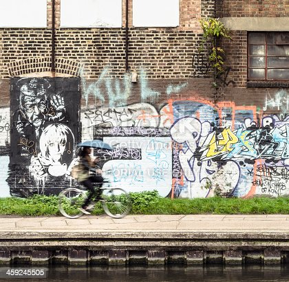 London, UK - November 1, 2013: Motion blur as a woman cycles past graffiti on the Regent's Canal towpath in Hackney, East London.