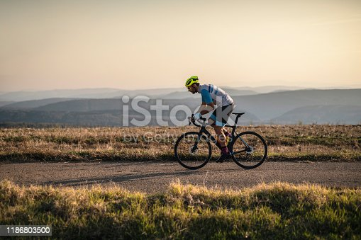 Athlete on racing bike outdoors at sunset.