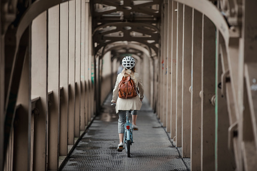 Rear view, wide angle shot of a unrecognisable person cycling to work over a bridge.