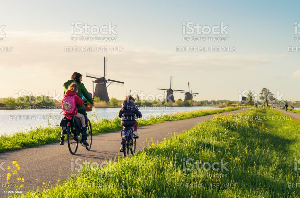 Cycling past windmills at Kinderdijk in Holland stock photo