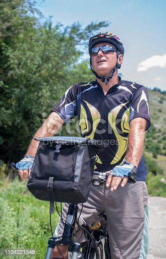 518659854istockphoto Cycling. Senior man on his mountain bike outdoors 1124221348