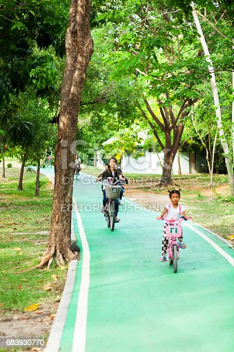 Capture of cycling and happy smiling thai woman on bicycle lane in Rod Fai Park in Bangkok Chatuchak. In foreground a girl is cycling.