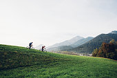 Young couple is cycling in nature. Mountains are in the back.