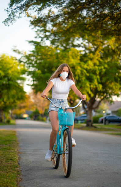 Cycling using protective face mask Cycling using protective face mask avoidance stock pictures, royalty-free photos & images