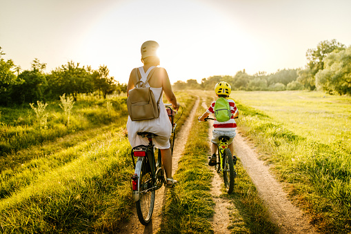 Photo of a young boy riding a bicycle with his mother on a beautiful sunny day in nature