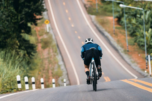 Cyclist adjusting posture to reduce air resistance. In the bike down the hill. Cyclist adjusting posture to reduce air resistance. In the bike down the hill. steep stock pictures, royalty-free photos & images