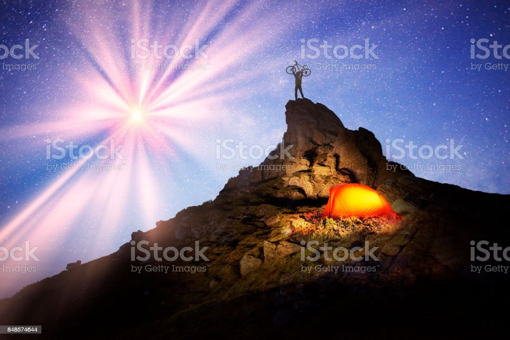 Cyclist and overnight on the rocks stock photo