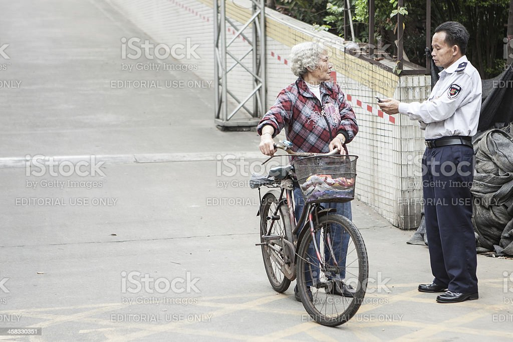 Cyclist and policeman having a discussion in China stock photo