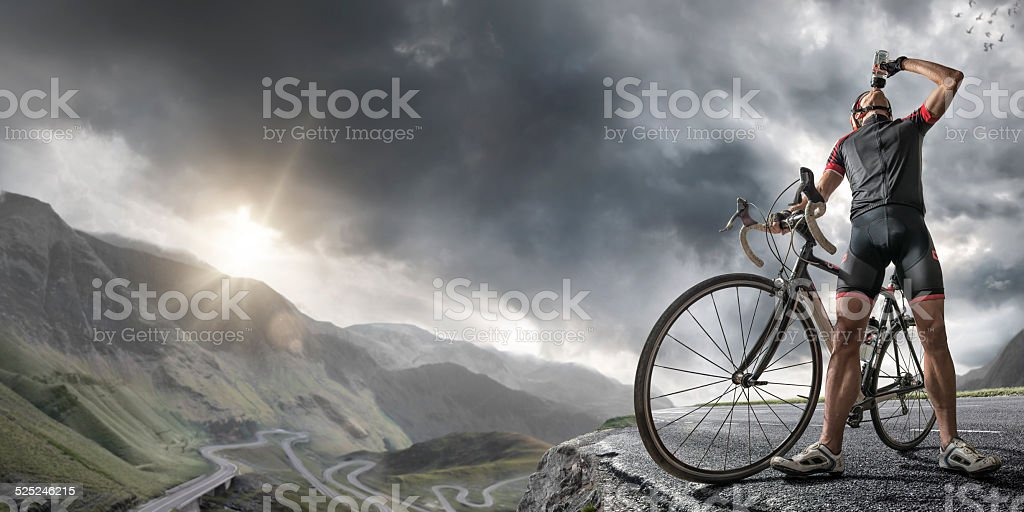Cyclist At Peak Of Mountain Road stock photo