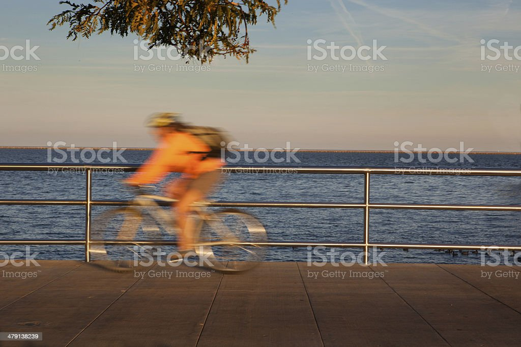 Cyclist becomes a blur along Lake Michigan in Milwaukee Wisconsin stock photo