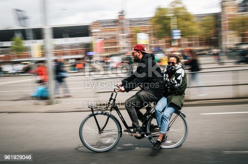 Amsterdam, Netherlands - 27 April, 2017: A man cyclist carries a young woman as passenger on a bicycle, riding through the street of Amsterdam, Netherlands. Motion blur.