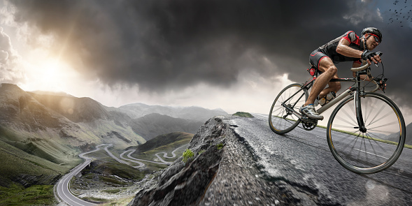 Wide angle close up image of a cyclist riding on a the peak of a road winding through mountains in a generic location, under a dramatic stormy evening sky at sunset. The bike is generic and cyclist is wearing an unbranded cycling suit, helmet and sunglasses. With intentional lighting effects.