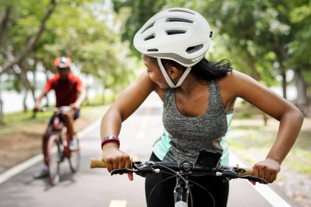 cyclist couple riding bikes in a park - kask sportowy zdjęcia i obrazy z banku zdjęć