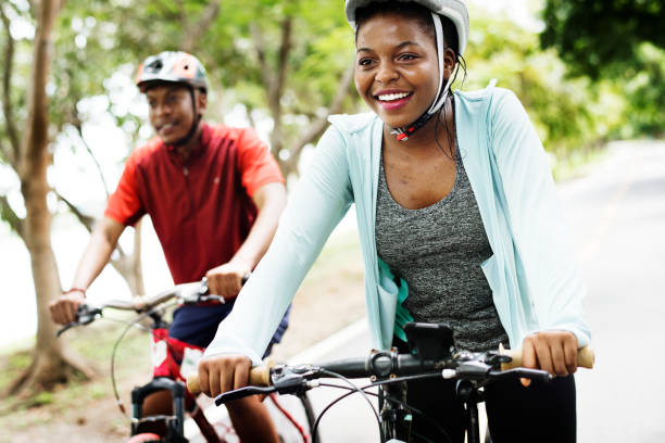 coppia di ciclisti che cavalcano insieme in un parco - ciclismo foto e immagini stock
