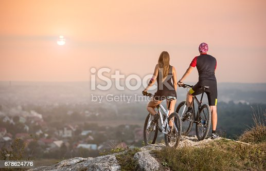 istock Cyclist couple with mountain bikes on the hill at sunset 678624776