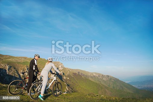 istock Cyclist couple with mountain bikes standing on the hill under the evening sky and enjoying bright sun at the sunset. 838466920