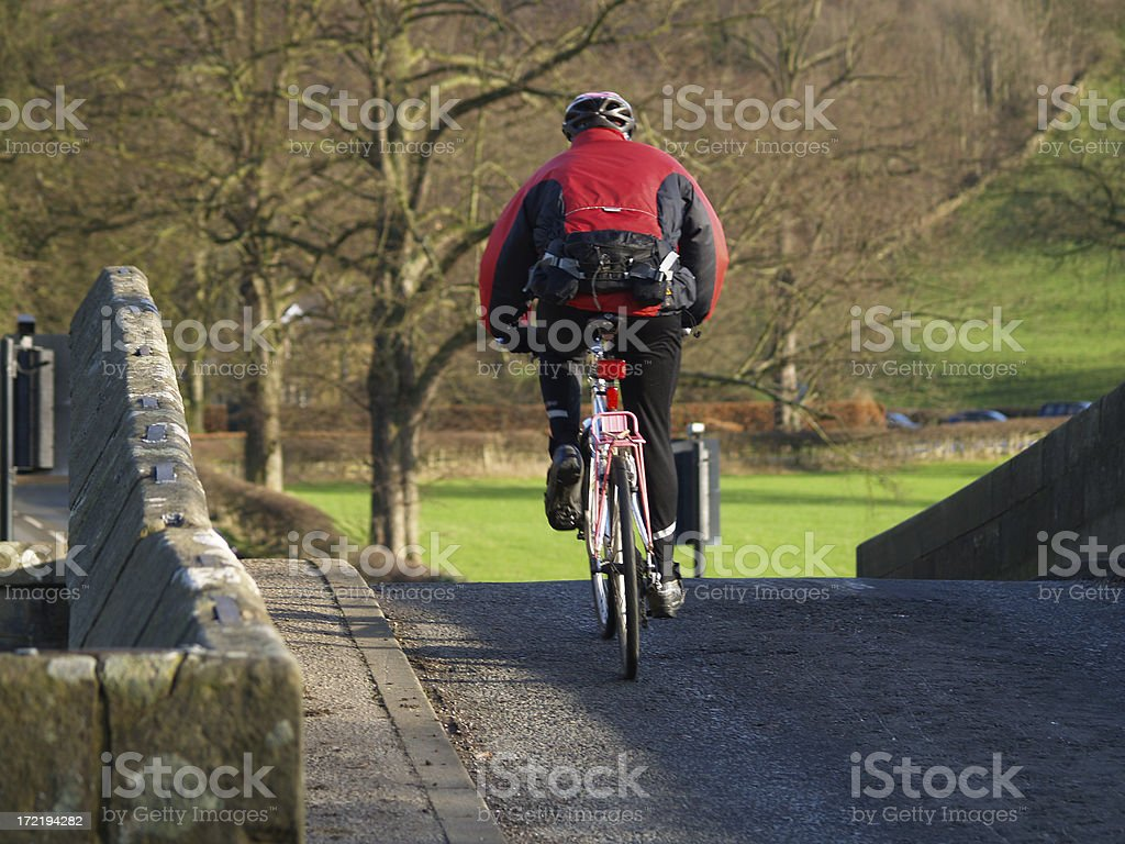Cyclist crossing bridge royalty-free stock photo