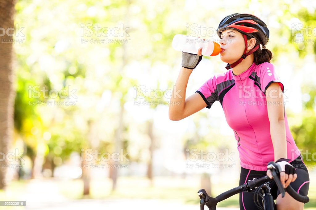 Cyclist Drinking Water While Riding Bicycle stock photo