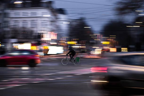 ein radfahrer fährt in der dämmerung über eine straße-kreuzung - radwege deutschland stock-fotos und bilder