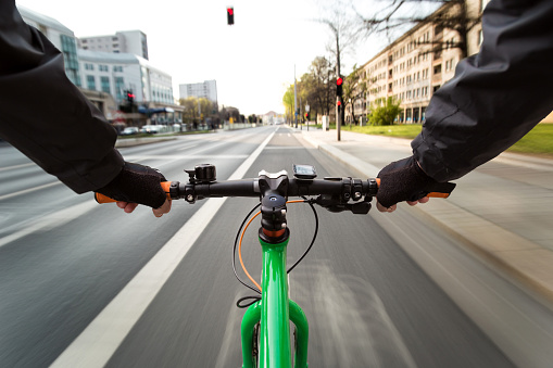 Cyclist drives on the bike path to a red traffic light - First-person view of cyclist/ motion blur