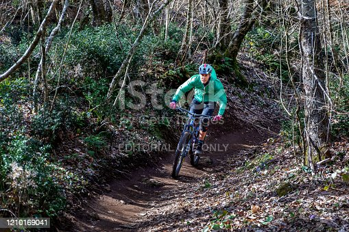 Rocca di Papa, Italy - February 29, 2020: Mountain bike cyclist runs on the country path, pedaling quickly downhill. Around him the thick vegetation with trees and green leaves on a spring day.