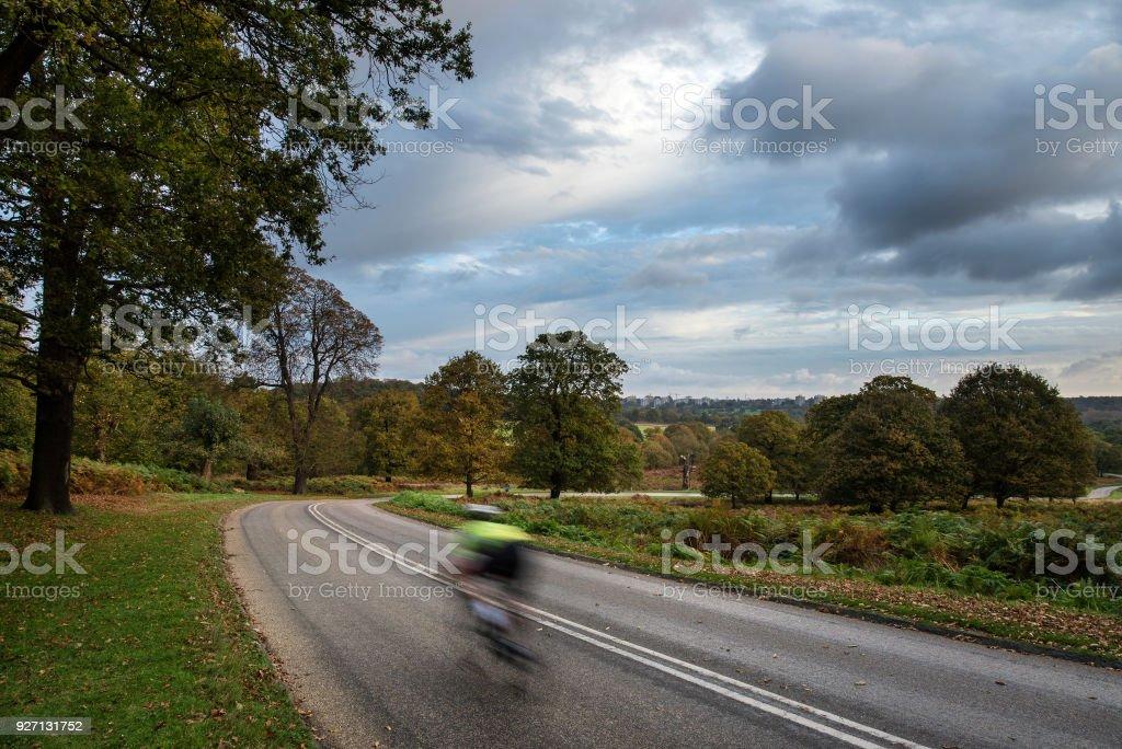Cyclist in beautiful Richmond Park Landscape in Autumn stock photo