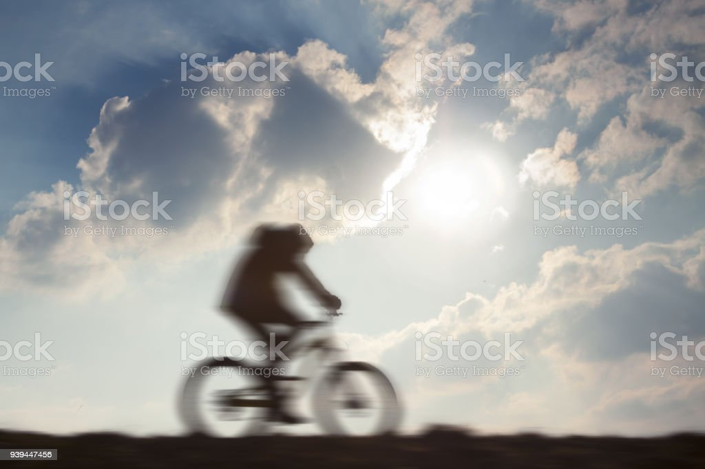 Cyclist in motion against sun stock photo