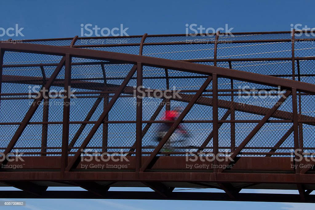 Cyclist in motion on bridge royalty-free stock photo