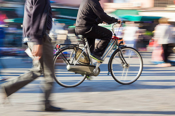 radfahrer in bewegung - fußgänger stock-fotos und bilder