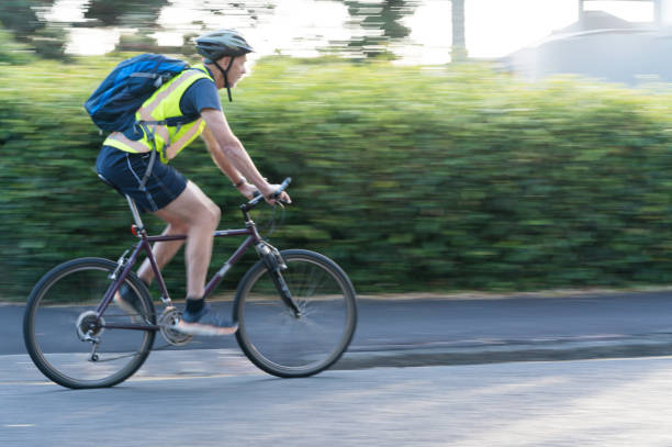 Cyclist in suburban street Cyclist riding past in suburban street Auckland New Zealand reflective clothing stock pictures, royalty-free photos & images