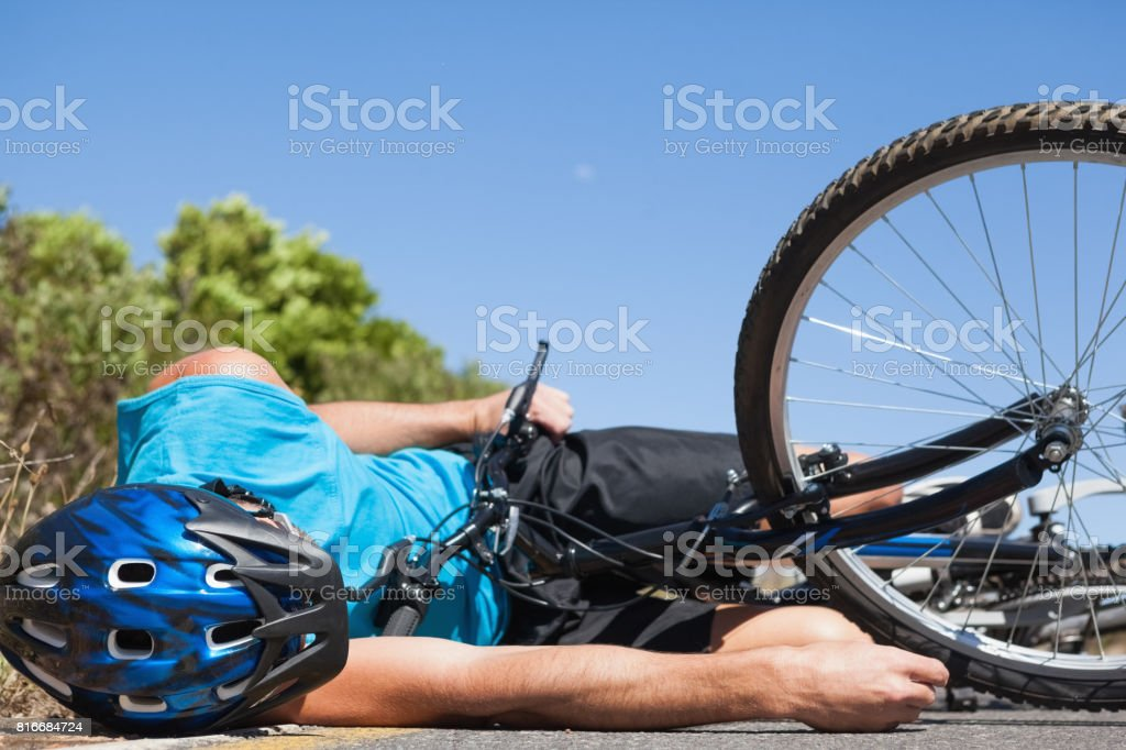 Cyclist lying on the road after an accident stock photo