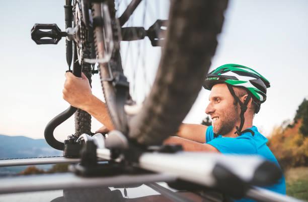 radfahrer-mann halten sein fahrrad auf dem autodach - fahrradhalter stock-fotos und bilder