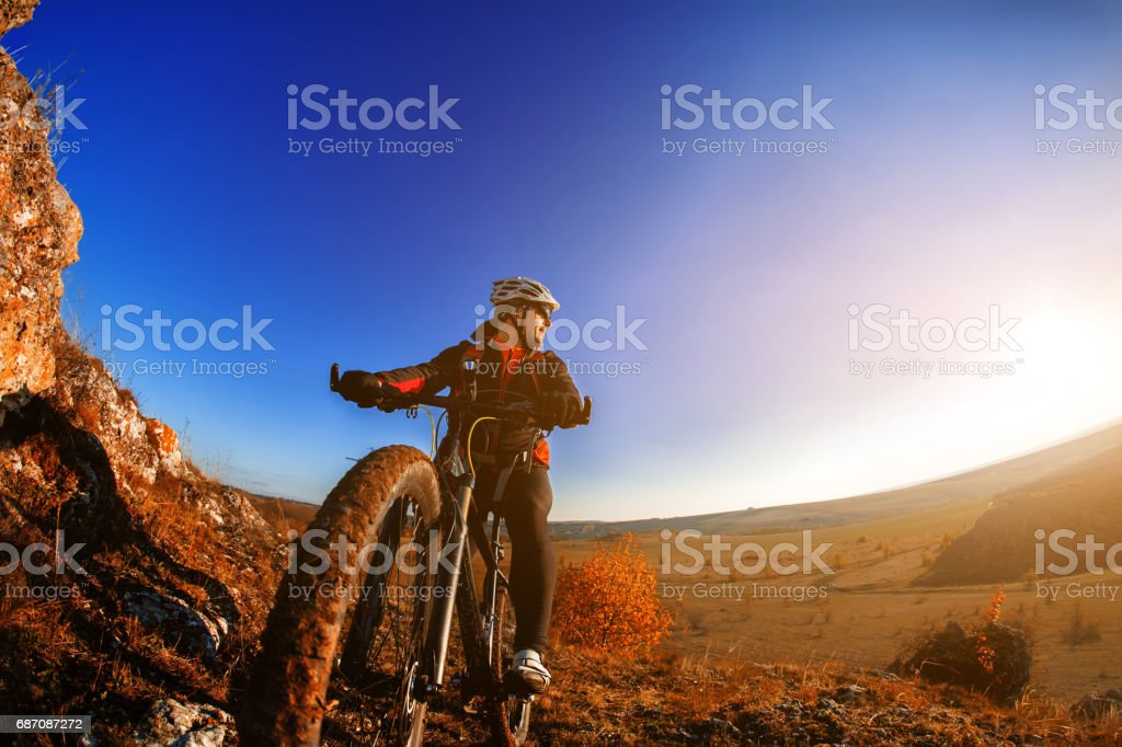 Cyclist man standing on a hill with bicycle and enjoying landscape on a sunny day against a blue sky Lizenzfreies stock-foto