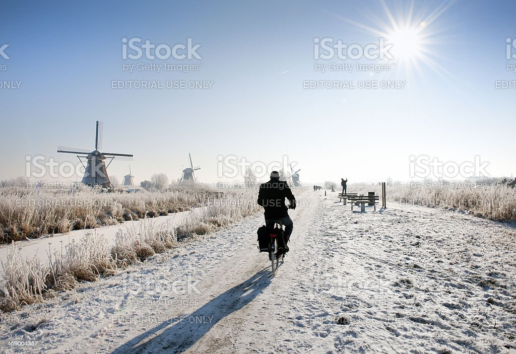cyclist near windmills at Kinderdijk in wintry landscape stock photo