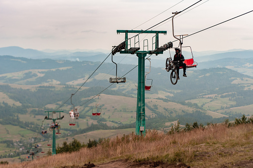 cyclist on a cable car, funicular in the mountains
