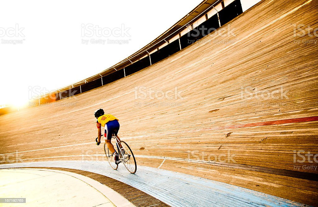 Cyclist on a velodrome track riding towards the evening sun stock photo