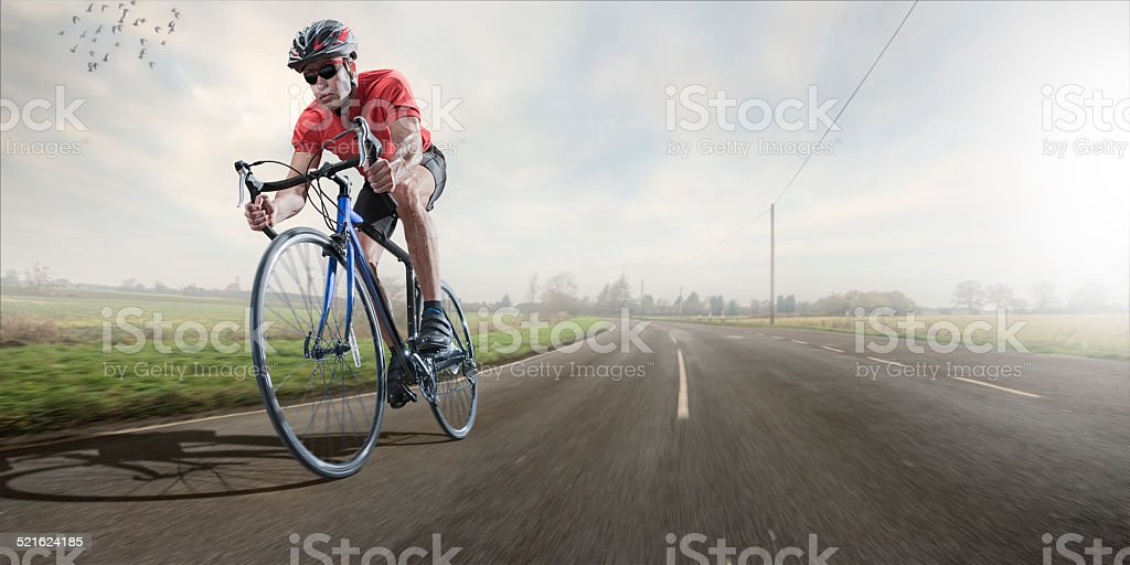 Cyclist on Early Morning Ride in Country stock photo