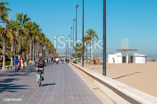 El Cabanyal in Valencia, Spain, with incidental people visible walking or cycling down the promenade